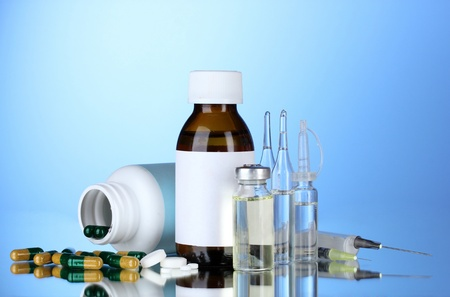 Medical bottles, ampoules and pills on blue background photo