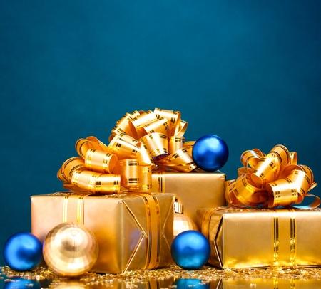 gifts: Mooie geschenken in goud verpakking en Kerst ballen op blauwe achtergrond