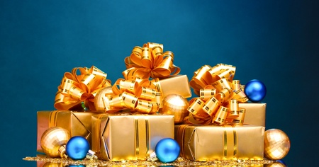 Beautiful gifts in gold packaging and Christmas balls on blue background Stock Photo - 10564935