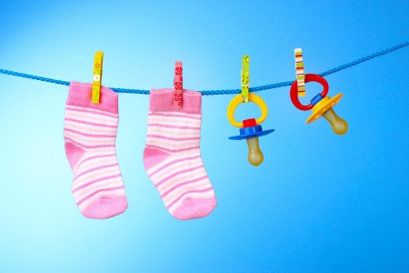 clothes pins: baby booties and nipple on a blue background Stock Photo