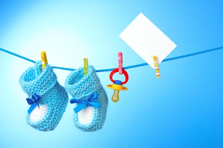 nipple: baby booties, nipple and white card on a blue background