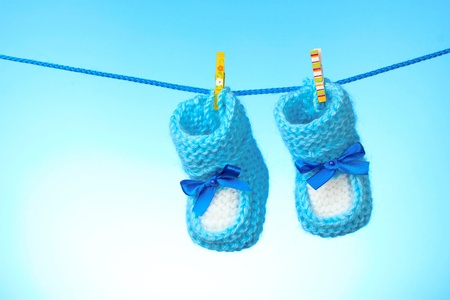 baby booties from a rope on a blue background photo