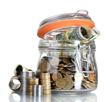 gratuity: Clear glass jar for tips with money isolated on white Stock Photo