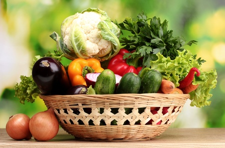 Fresh vegetables in basket on  wooden table on green background photo
