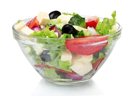 Deliciosa ensalada griega en un recipiente transparente aislado en blanco