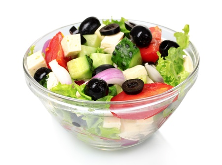 Tasty greek salad in transparent bowl isolated on white photo