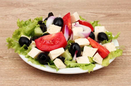 Tasty greek salad on plate on wooden background photo