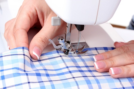 sewing machine, blue fabric and womens hands photo