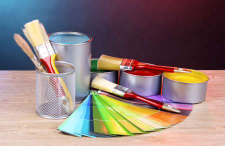 Open cans with bright colors, brushes and palette on wooden table photo