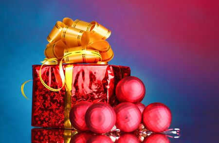 beautiful gift with gold bow and Christmas balls on blue background Stock Photo - 10753983