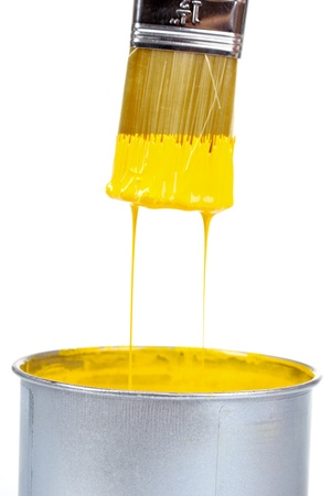 open can of yellow paint and brush isolated on white photo