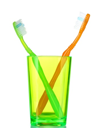 tidiness: green and orange toothbrushes in glass isolated on white