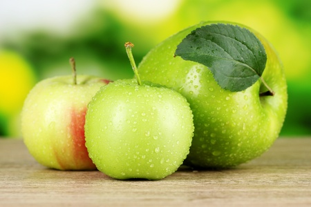 Fresh organic apples on wooden table isolated on white photo