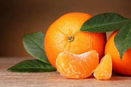 Rijpe oranje mandarijnen met segmenten op bruine achtergrond Stockfoto