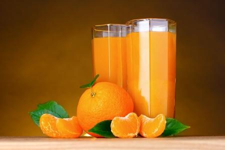 sweet table: Glasses of healthy fresh juice of mandarins on brown background