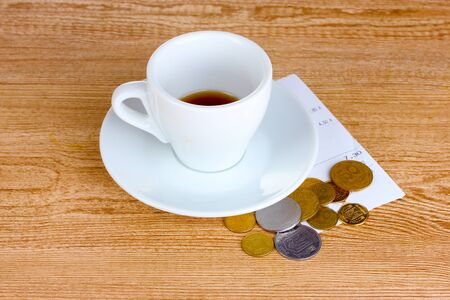 Empty cup of coffee with coins tip on wooden background photo