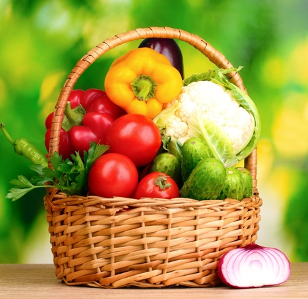Fresh vegetables in basket on  wooden table on green background