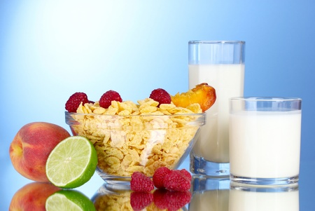 corn flakes: tasty cornflakes, fruit in glass bowl and milk on blue background