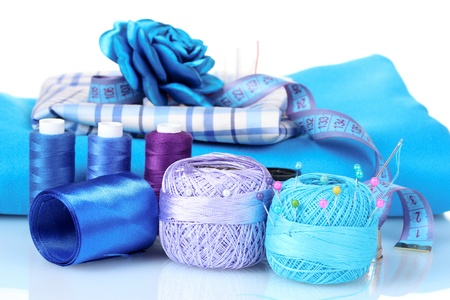 bright blue yarn, fabric, satin ribbon and measuring tape isolated on white photo