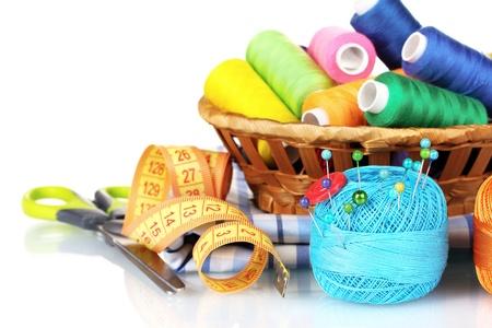kit de costura: temas brillantes en la canasta, tijeras y cinta métrica aislados en blanco