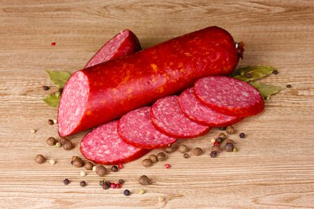 Tasty sausage and spices on wooden background photo