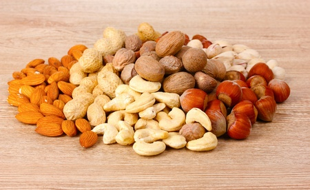 nutmeg, peanuts, hazelnuts and almonds on wooden background Stock Photo - 10817513