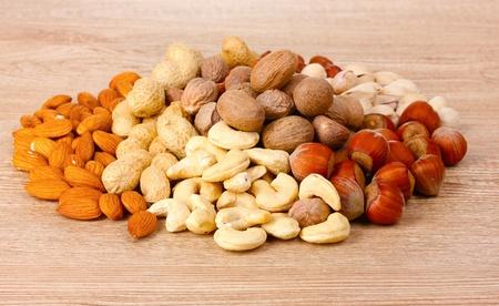 nutmeg, peanuts, hazelnuts and almonds on wooden background Stock Photo - 10817513