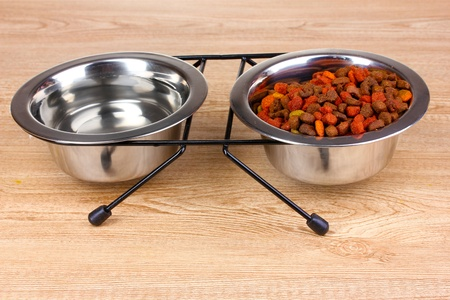 Dry cat food and water in bowls on wooden background photo