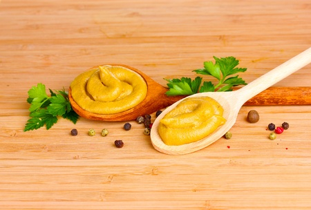 Mustard in wooden spoons, spices and parsley on wooden background photo