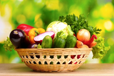 Fresh vegetables in basket on  wooden table on green background Stock Photo - 10928943