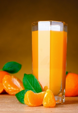 Glass of healthy fresh juice of mandarins on brown background photo