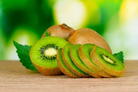 kiwi fruit: Juicy kiwi fruit on wooden table on green background Stock Photo