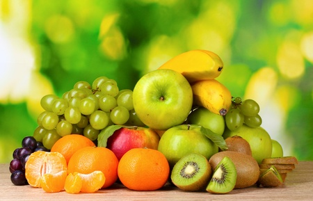 Ripe juicy fruits on wooden table on green background Foto de archivo