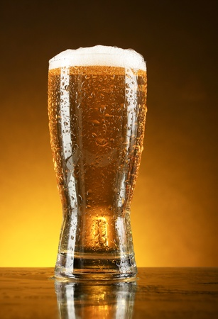 Glass of beer on dark background photo