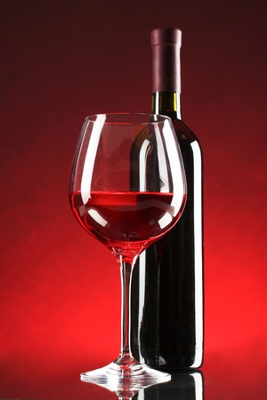 bottle of wine and glasses on red background photo