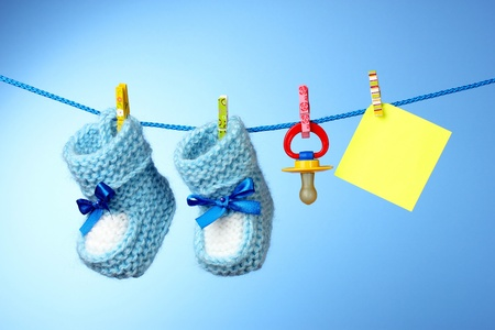 baby booties, nipple and yellow card on a blue background photo