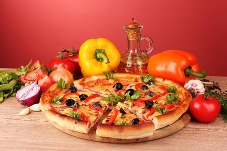 pizza: Pizza y verduras sobre fondo rojo Foto de archivo