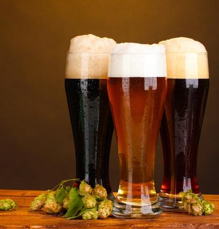 brouwerij: drie glazen met verschillende bieren en spring op houten tafel op bruine achtergrond Stockfoto