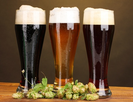 three glasses with different beers and hop on wooden table on brown background Stock Photo - 11069158