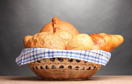 delicious bread in basket on wooden table on gray background Stock Photo - 11069127