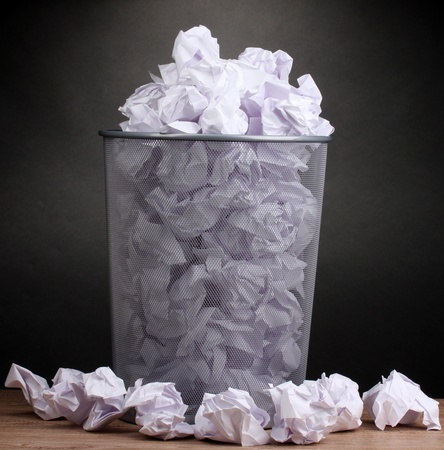 wastepaper basket: Metal trash bin from paper on wooden floor on gray background