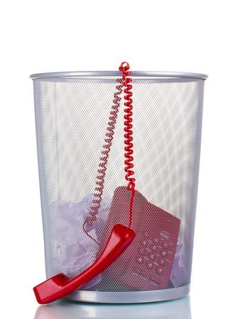 �garbage: tel�fono rojo y el papel en un cubo de basura de metal aisladas en blanco Foto de archivo