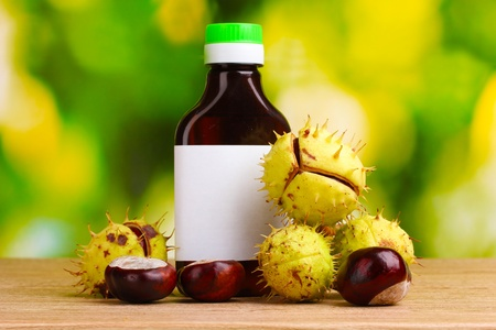 chestnuts and medical bottle on wooden table on green background photo