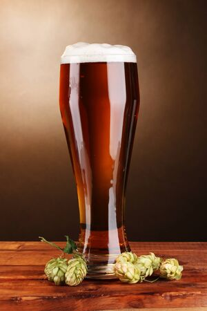 beer in glass and green hop on wooden table on brown background photo
