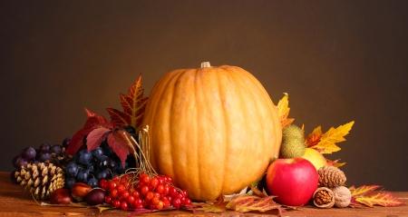 toppa: di zucca, mele, bacche e foglie su tavola di legno su sfondo marrone Archivio Fotografico