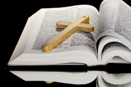 Russian bible and wooden cross on black background photo
