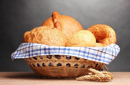bread basket: delicious bread in basket and ears on wooden table on gray background Stock Photo