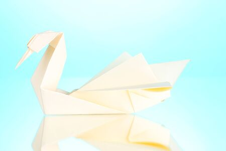 Origami paper swan on blue background photo
