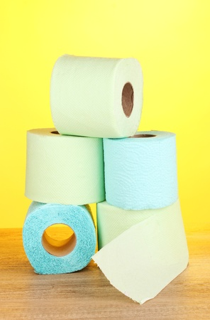green and blue rolls of toilet paper on wooden table on yellow background photo