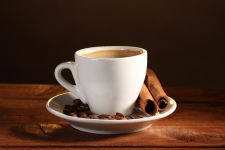 cup with coffee, cinnamon and coffee beans on  wooden table on brown background Stock Photo - 11186707